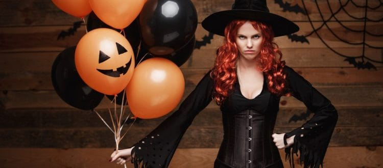 Halloween Witch Concept – Beautiful caucasian woman in witch costumes celebrating Halloween posing with posing with orange and black balloon over bats and spider web on Wooden studio background.